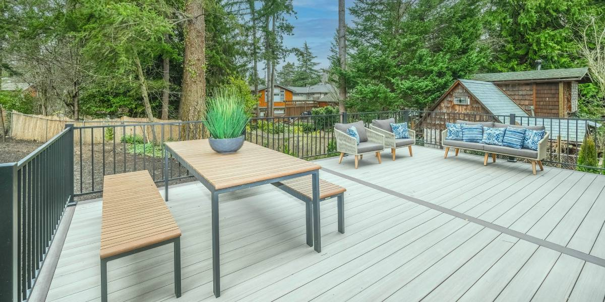 a backyard deck with outdoor seating looking out at trees and sky