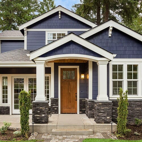 blue home featuring a grey roof and white columns with a stone base