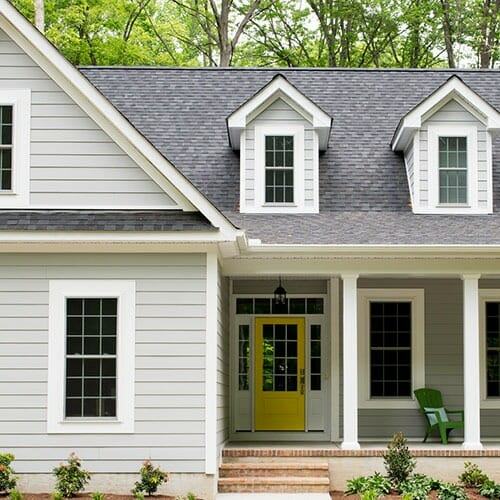 Grey-roofed home with a yellow door and a green lawn chair on the porch