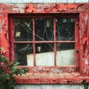 old red window with peeling paint and cracked glass