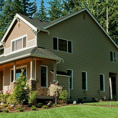 Side of a two-story home painted in earth tones with a mowed lawn