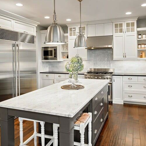 White and grey themed kitchen equipped with stainless steel appliances
