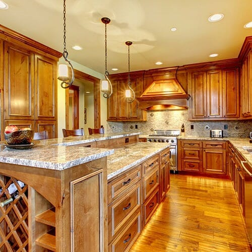Wood-paneled kitchen with marble countertops and wine rack