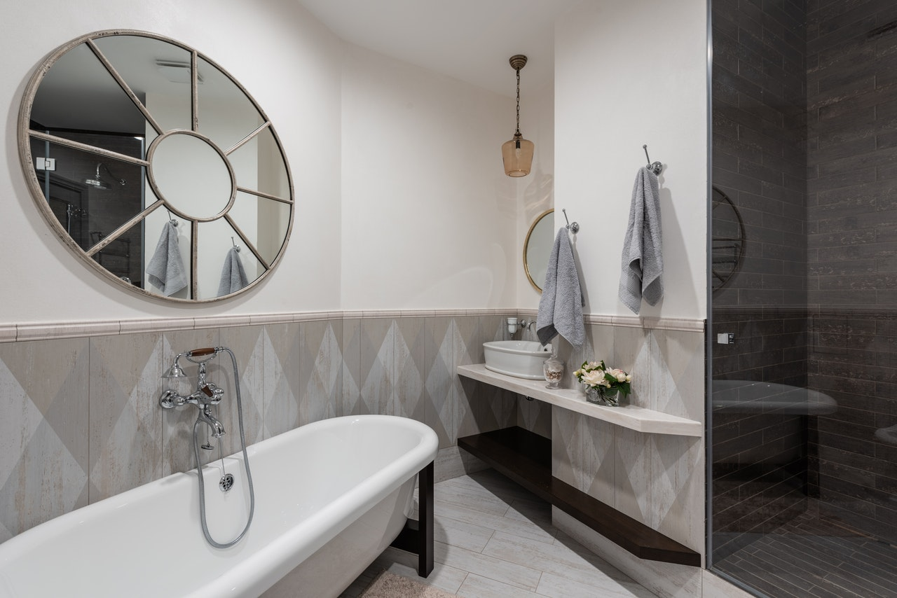 newly renovated and financed bathroom with circular mirror