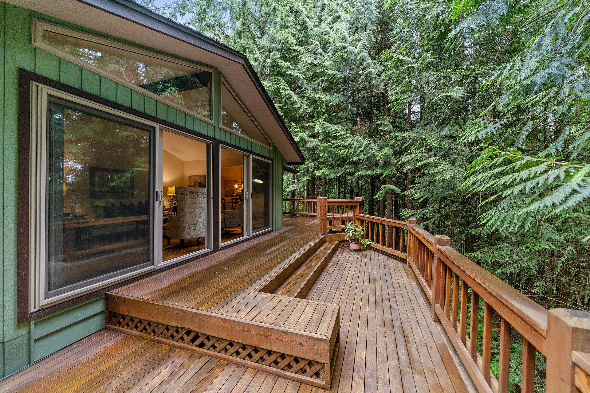 Outdoor deck by green house and pine trees